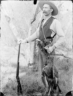 Self-portrait of Charles Elliott Gill holding a rifle and dead turkey (MSA)