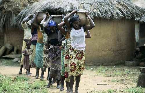 Young women and girls carry water