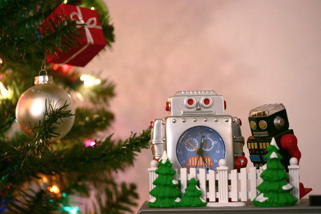 A photo of two toy robots in front of a Christmas tree