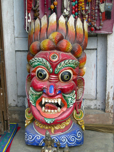 Large painted three eyed wrathful wood mask, yellow hair standing up, earrings, necklace, bushy eyebrows, mustache and goatee, kusha grass, Swayambu, Kathmandu, Nepal by Wonderlane
