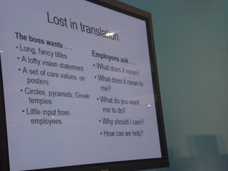 A PowerPoint slide with the differences between what bosses present (pie charts, lofty vision statements) and what employees want to hear (how can I help?)