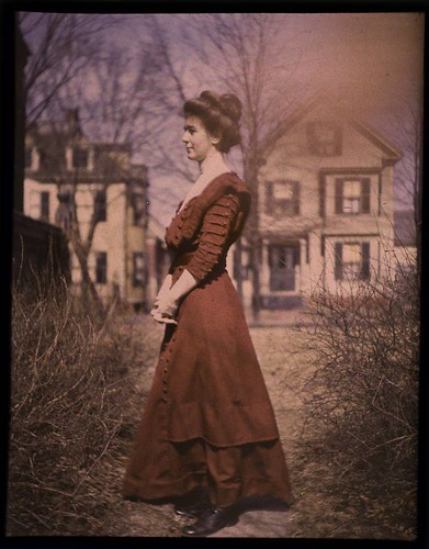 Woman wearing red dress with houses in background