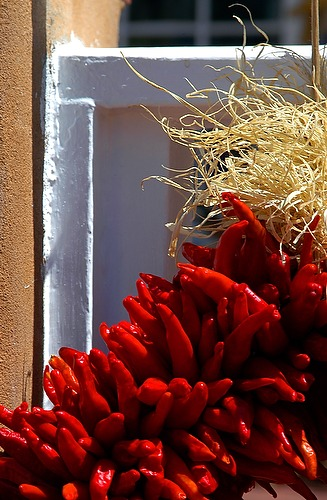 Decorative red chili pepper wreath hanging on an adobe and white fence in Santa Fe, New Mexico.