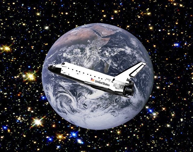 Space Shuttle Discovery cruising in space over the earth ...