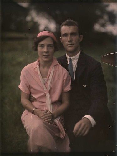 Couple posing crouched in a garden.  She is wearing a pretty pink Edwardian-style dress, light pink scarf and pink pillbox hat.  He is wearing a suit.