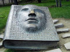 Chinese bronze sculpture, face emerging from book