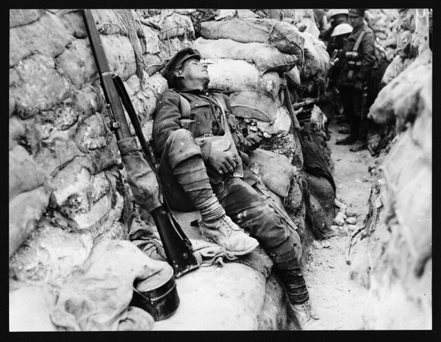 Soldier's comrades watching him as he sleeps, Thievpal, France, during World War I