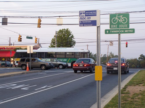 Bicycle route sign pointing to the Twinbrook Metro and a RideOn bus stop sign and a RideOn bus