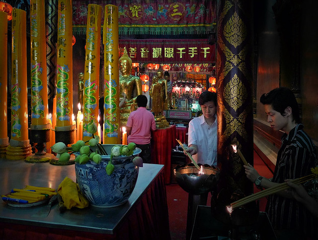 Lighting joss sticks as an offer to the gods