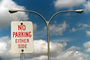 a street lamp with two lamps extending to either side of a metal pole. To the left a sign that reads No Parking on Either Side.