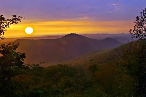 blue trees sky orange sun mountains sunrise landscape