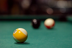 recreation(0.0), cue stick(0.0), carom billiards(0.0), indoor games and sports(1.0), snooker(1.0), sports(1.0), nine-ball(1.0), pool(1.0), billiard table(1.0), games(1.0), billiard ball(1.0), eight ball(1.0), close-up(1.0), english billiards(1.0), ball(1.0), cue sports(1.0),