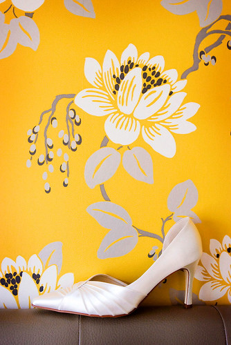 Wedding Photos bridal shoe perched on sofa against a floral wallpaper