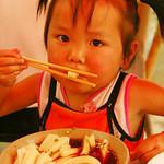 Little Girl Eating Noodles - Guizhou Province, China