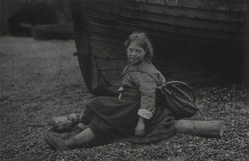 'At Auchmithie 1881'. Girl with basket sitting on shore in front of boat