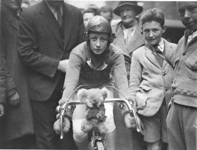 Close-up of Billie Samuels on the Malvern Star bike showing her koala bear mascot before leaving for Melbourne, 4 July 1934, by Sam Hood