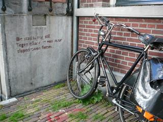 La leyenda en la pared dice en holandes algo bonito sobre dos bicicletas descansando en la pared, como lo estan haciendo
