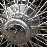 "Old Jaguar E-type sports car: hubcap sprocket text ""UNDO --> RIGHT (OFF) SIDE"""