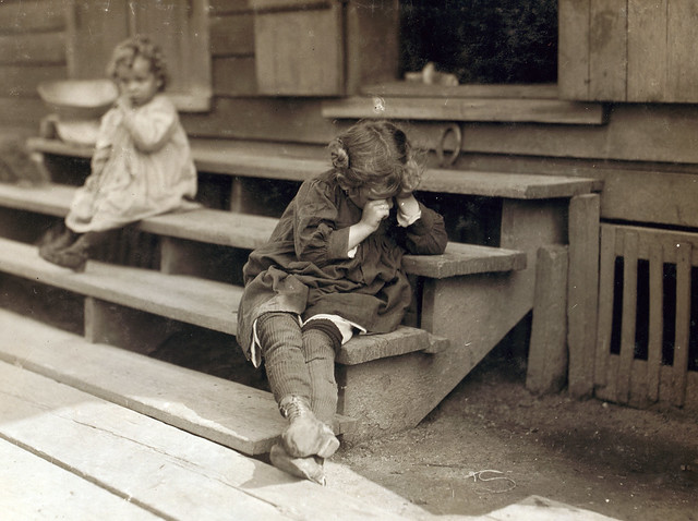 5 yr old after day's work that began at 5 AM, was tired and refused to be photographed, the mother said, 'Oh, She's ugly,' said picking shrimp was very hard on the fingers, Biloxi, MS, by Lewis Wickes Hine 1911