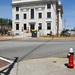 Some scraps of misc at the bottom of the frame of a photo of a county courthouse and its portalet in the U.S. South.
