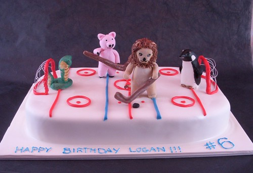 Animals playing hockey cake