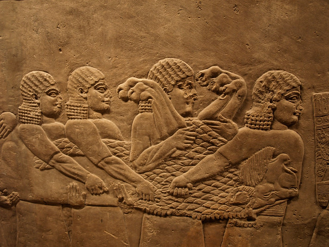Assyrian relief carving men carrying dead lion flickr