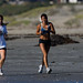 Two young girls jog along Morro Strand State Beach - Ethnic Diversity depicted