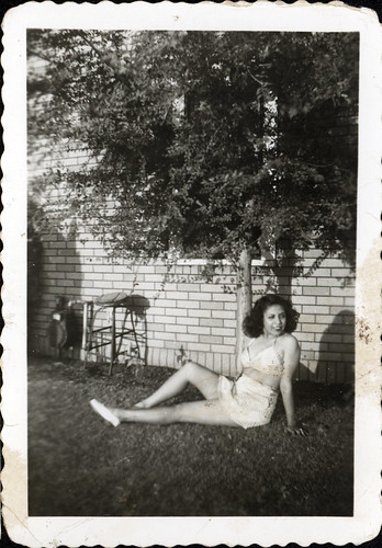 Girl in sun-suit in back yard