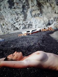 White skin on black sand in Santorini