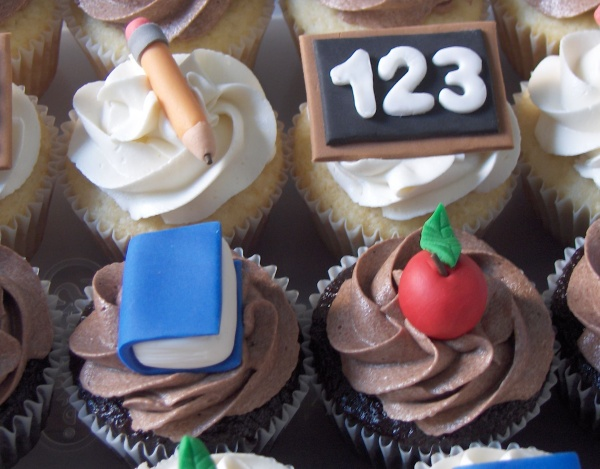 Four cupcakes with white and brown frosting and decorations of a pencil, a chalkboard, a book, and an apple.
