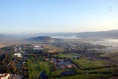paragliding(0.0), village(0.0), sea(0.0), cityscape(0.0), coast(0.0), town(1.0), mountain(1.0), bird's-eye view(1.0), mountain range(1.0), hill(1.0), landscape(1.0), aerial photography(1.0), rural area(1.0), panorama(1.0), flight(1.0), mountainous landforms(1.0),