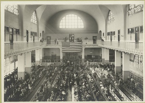 Immigrants seated on long benches, Main Hall, U.S. Immigration