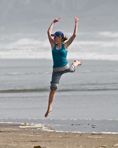 5 of 8 Girl dances at water's edge on Morro Strand State Beach