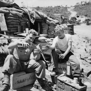Two unidentified soldiers enjoy some recreation time at a sandbagged Navy Army Air Force Institute (NAAFI)