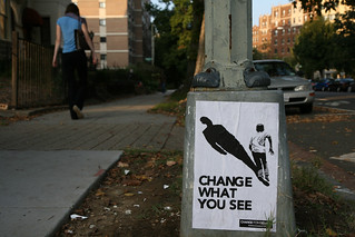 "Picture of a woman walking by a sandwich board that says ""Change what you see"""
