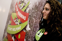 "An Oxfam activist standing in front of a giant ""Stop Harming - Start Helping"" Christmas card delivered to UN Climate negotiators in Poznan"
