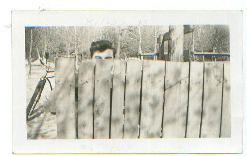 Man behind wooden fence -- Kilroy was here