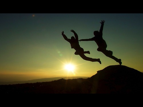 Two people jumping, with the sun rising in the background / CC-BY