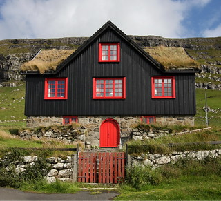 Black house, red windows, grass roof
