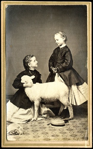 Two girls posed in studio with lamb
