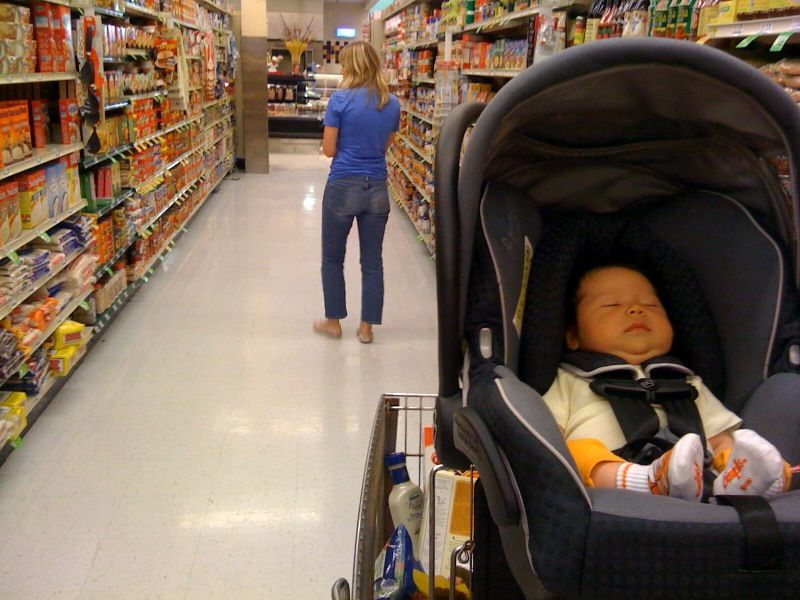 Mom grocery shopping with baby