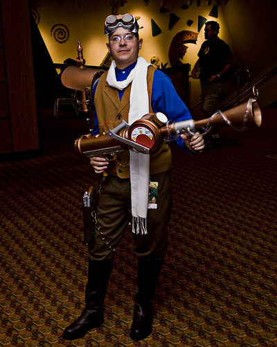 A steampunk guy holding a giant fake weapon