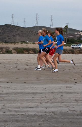 Morro Bay, CA High School Physical Education class - teen girls run up and down the Morro Strand State Beach