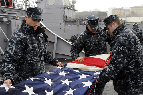 Sailors fold American flag on guided-missile destroyer USS Laboon (DDG 58)