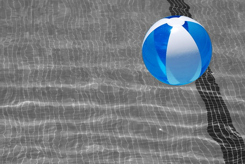 blue and white beach ball suspended over a pool