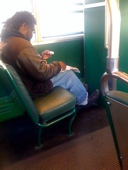 Dude rolling joints on the street car on the way to work