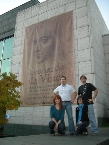 The group posing in front of the Da Vinci banner