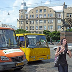 Ukraine, Lviv, buses & long-hair teen-girls with statue of Daniel of Galicia  in backdrop