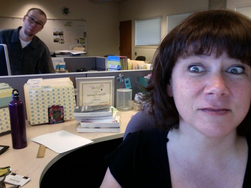 man looking over woman's shoulder at desk