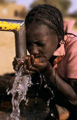 Young girl drinks fresh water from a pump